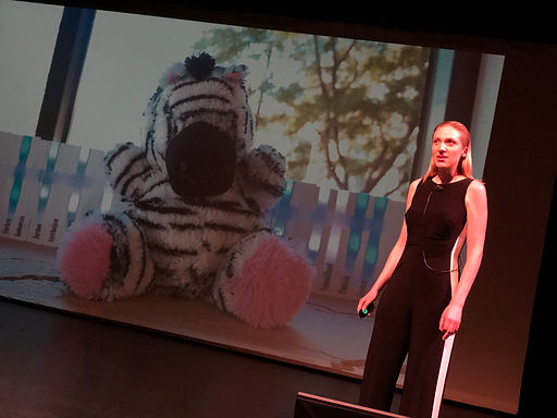 A photo of Layne Jackson Hubbard pitching MindScribe.org at Catalyze CU's Demo Day. She is standing on a stage with a large projector screen behind. The screen displays a stuffed animal zebra robot.