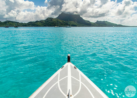Sailing in a tradional Polynesian outrigger canoe over the coral reefs of the Bora Bora Lagoon in French Polynesia.  Price List #1