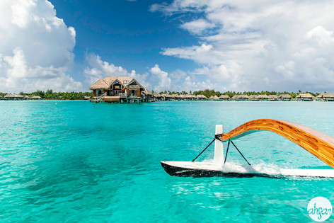Sailing on a tradional Polynesian outrigger canoe past overwater bungalows in Bora Bora, French Polynesia.  Price List #1