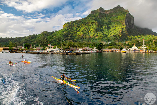 Locals racing outrigger canoes past the island of Bora Bora, French Polynesia.  Price List #1