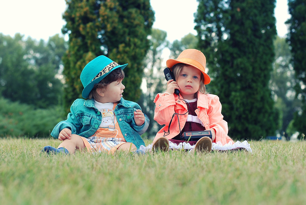 children dressed as adults sitting on grass