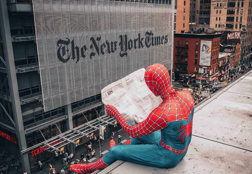 Spiderman reading a newspaper on a rooftop