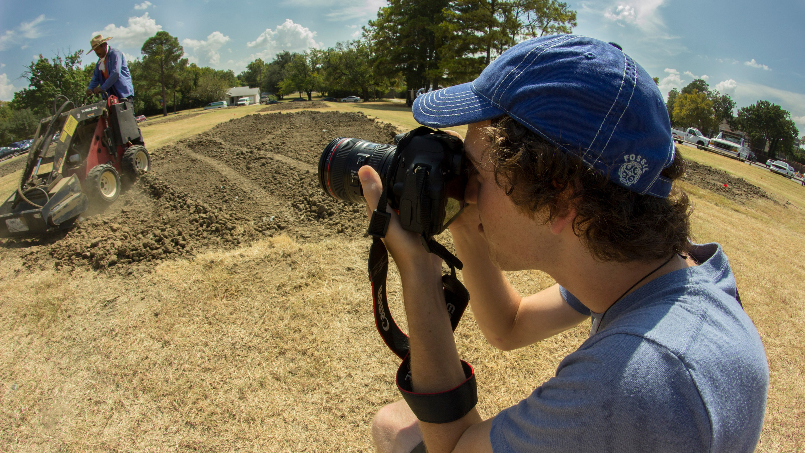 Rookie photographer Winston Henvey crouches to take a photo of workers preparing mud volleyball fields at UT-Arlington.