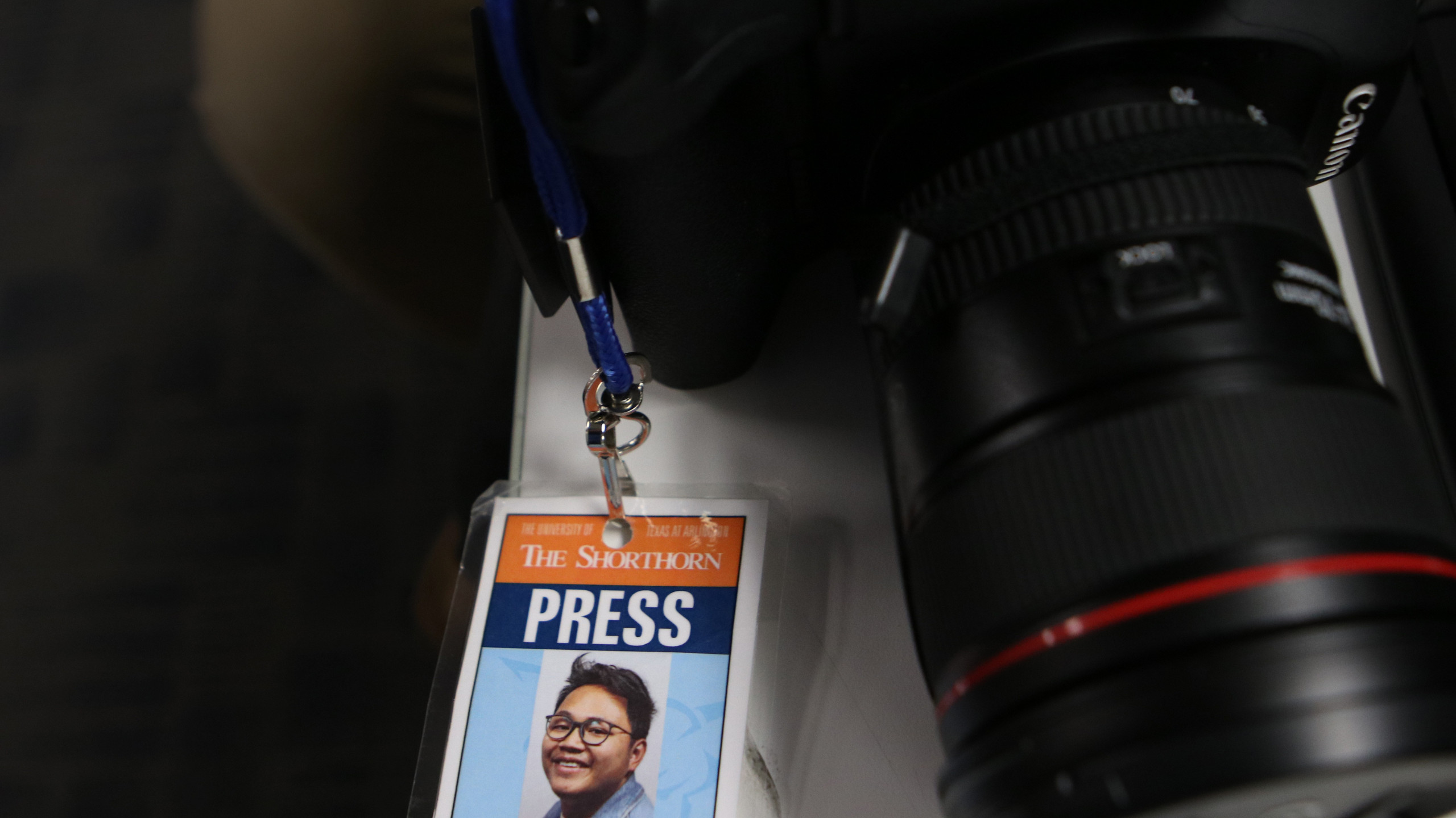 Duy Vu's press badge lays on a desk next to his camera.