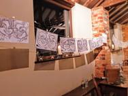 peg hanging caricatures at wedding