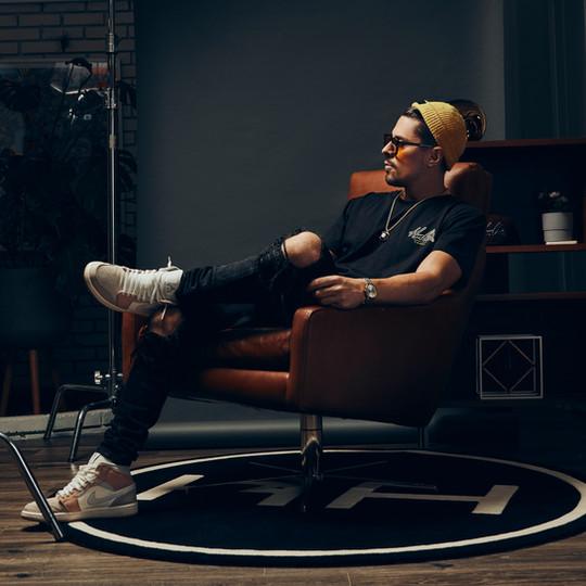 Male Model Wearing HMLTN Cursive Tee sitting in leather chair