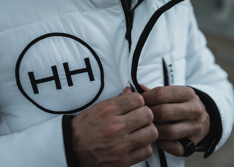 HH Clothing hyper parka features a full legth zip and button closures for a clean look
