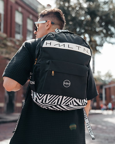 Hollywood Hamilton Clothing zig zag backpack being held by a model wearing all black