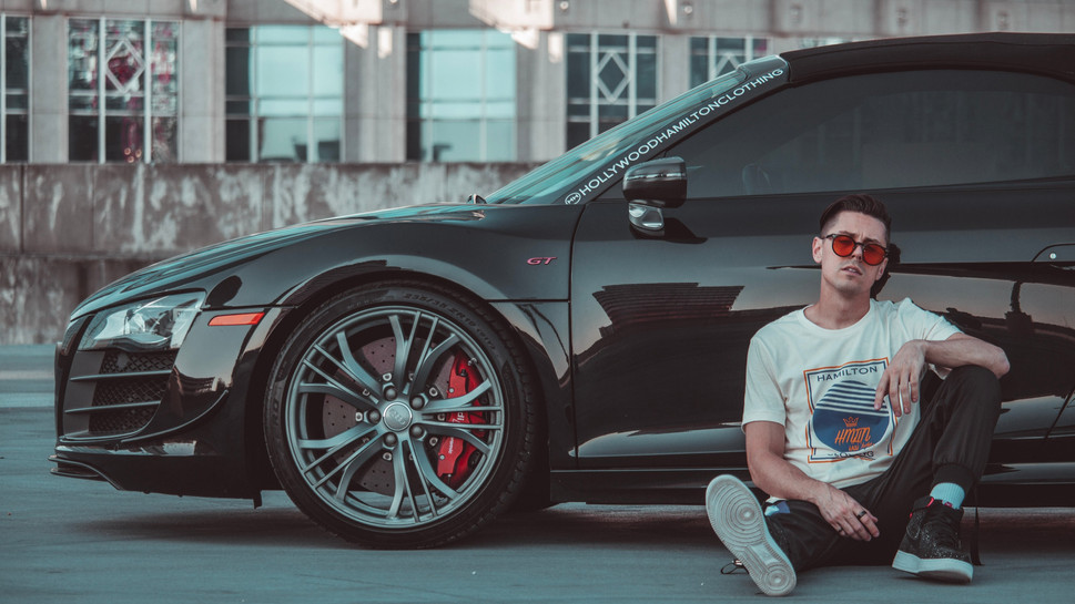 Hollywood Hamilton Clothing model wearing new arrival tee leaning on an audi r8