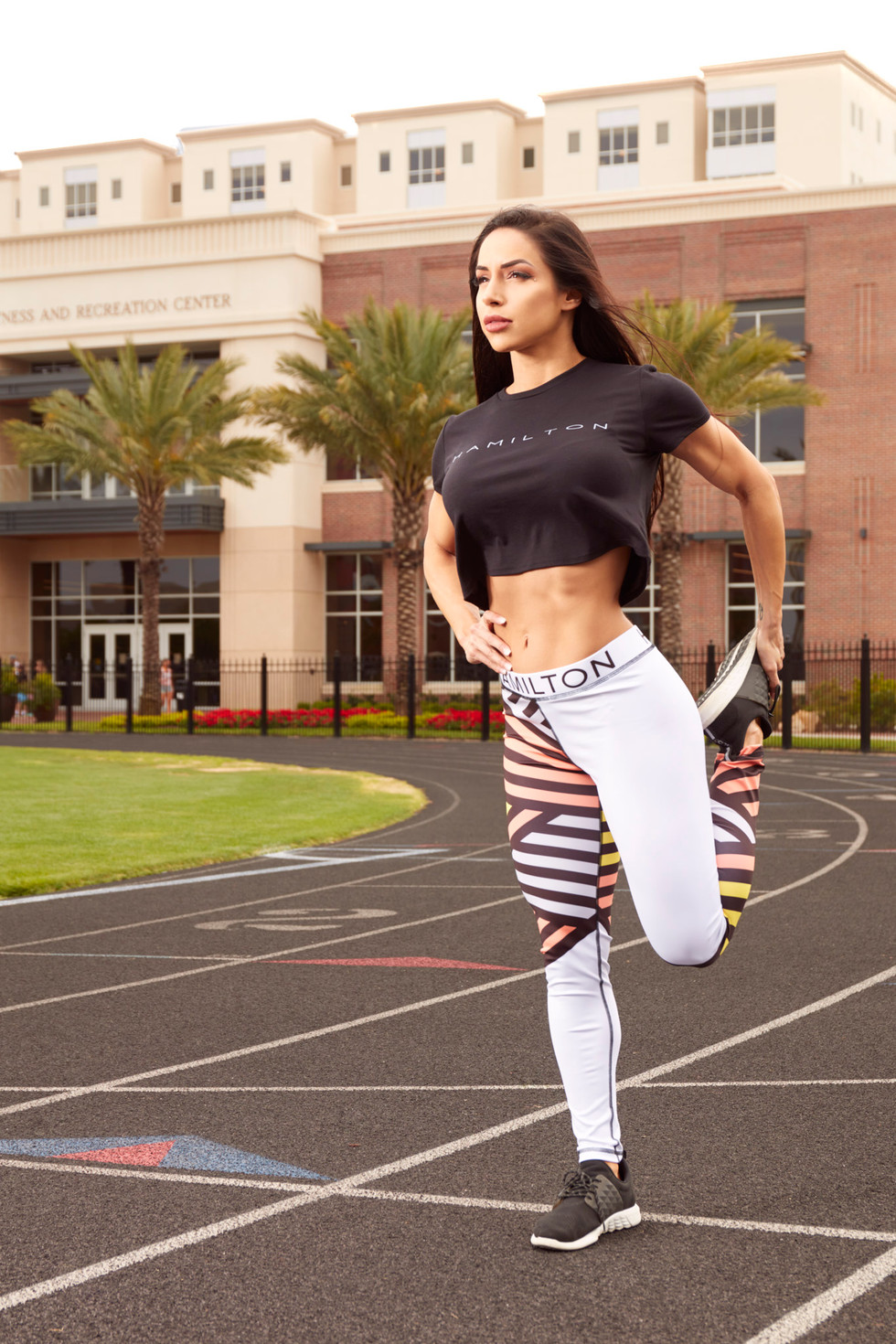 Hollywood Hamilton Clothing Women's Streetleisure Collection 2018 stretching in zig zag leggings and black crop top athleisure