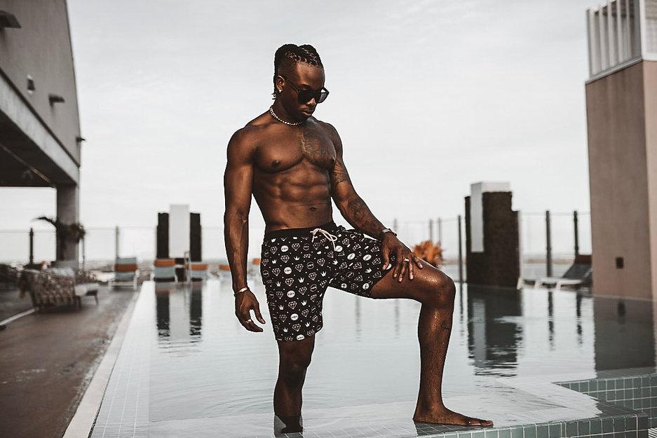 male model wearing crown jewels swim trunks in pool