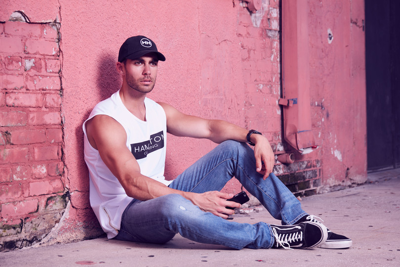 Hollywood Hamilton clothing male model wearing a classic logo black dad hat sitting against a pink brick wall