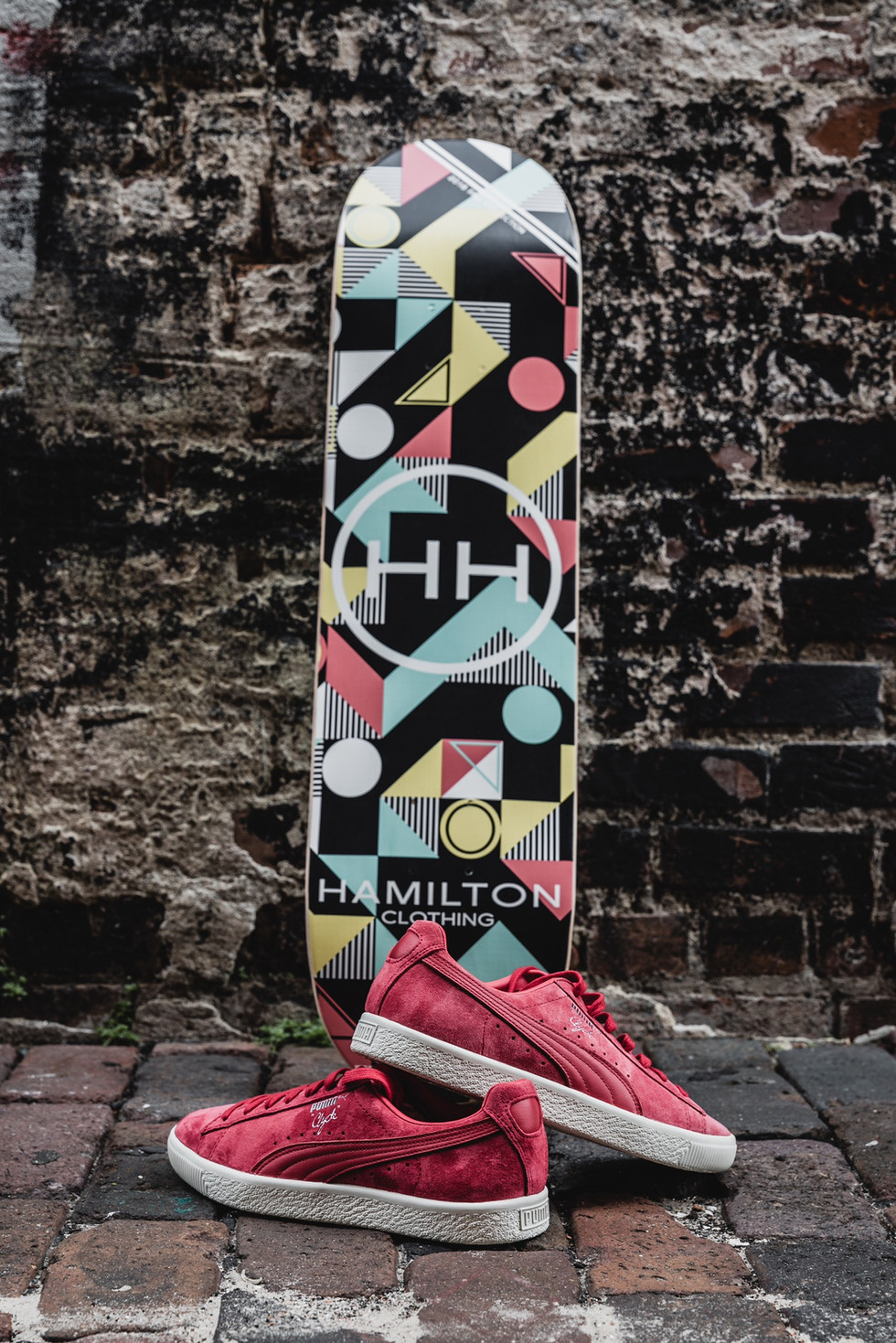 geometric skateboard deck close up with red puma sneakers
