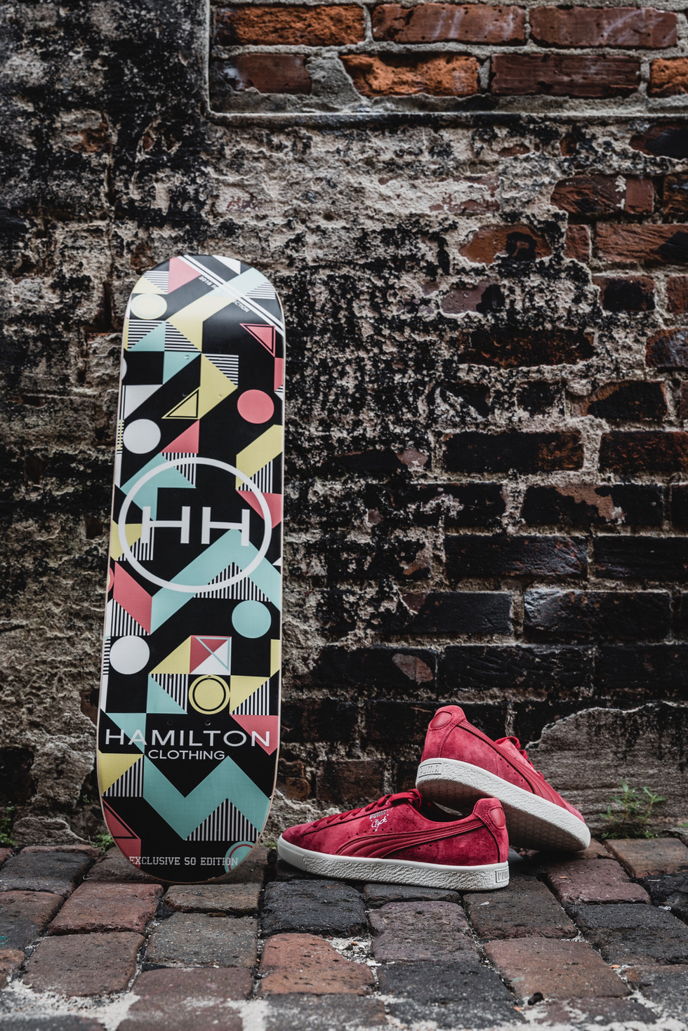 Geometric skateboard deck paired with red puma suede sneakers
