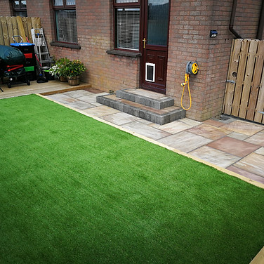 Artificial grass area level with existing bed. Ravena Flagging and charcoal edged steps.