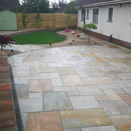 Large ravena patio with curved path. Tobermore walling, sunken artificial lawn and maintenance free gravel beds.