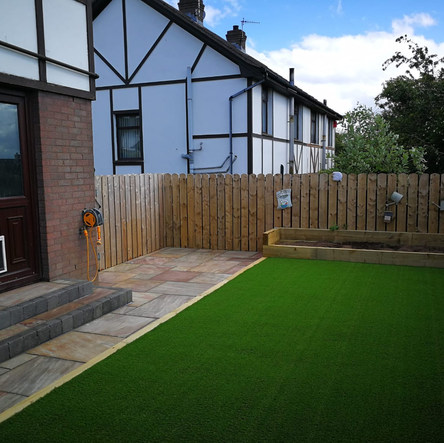 Ravena flagging with charcoal edging. 30mm artifical grass and sleeper bed. Child and pet friendly garden.