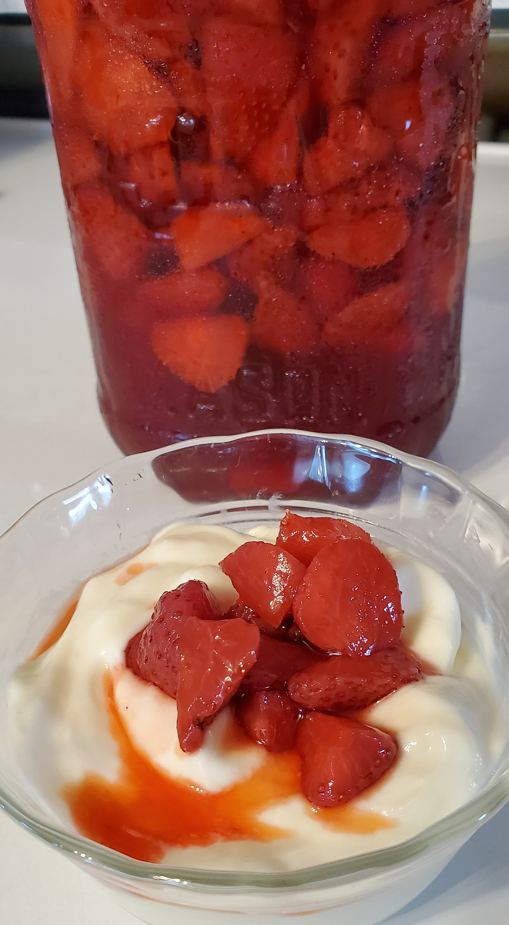 A bowl of yogurt sits on a stovetop. It is topped with a small amount of pickled strawberries. Behind the bowl is the jar of finished pickled berries. End photo ID.