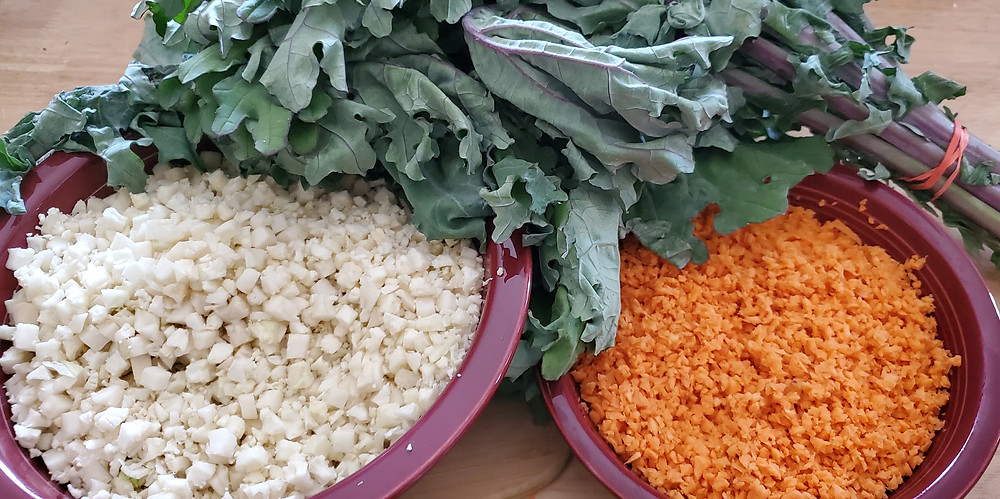 Two bowls are on a wooden countertop. In the left bowl is riced cauliflower. In the right bowl is riced sweet potato. Behind them are two bunches of kale. End photo ID.