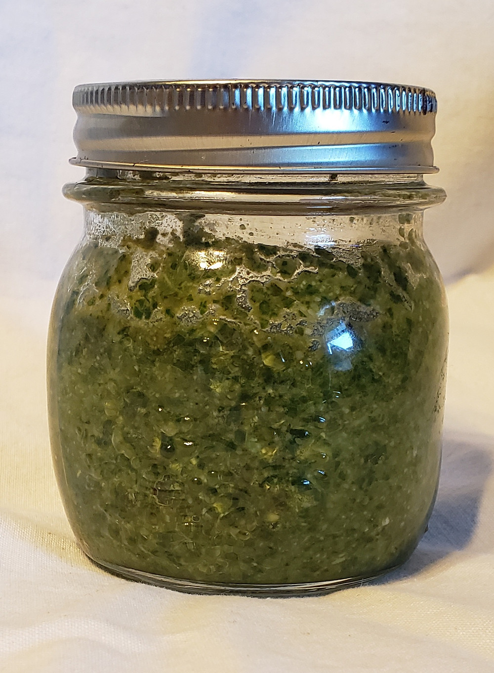A completed half pint jar of pesto with a silver lid on a white background. End photo ID.