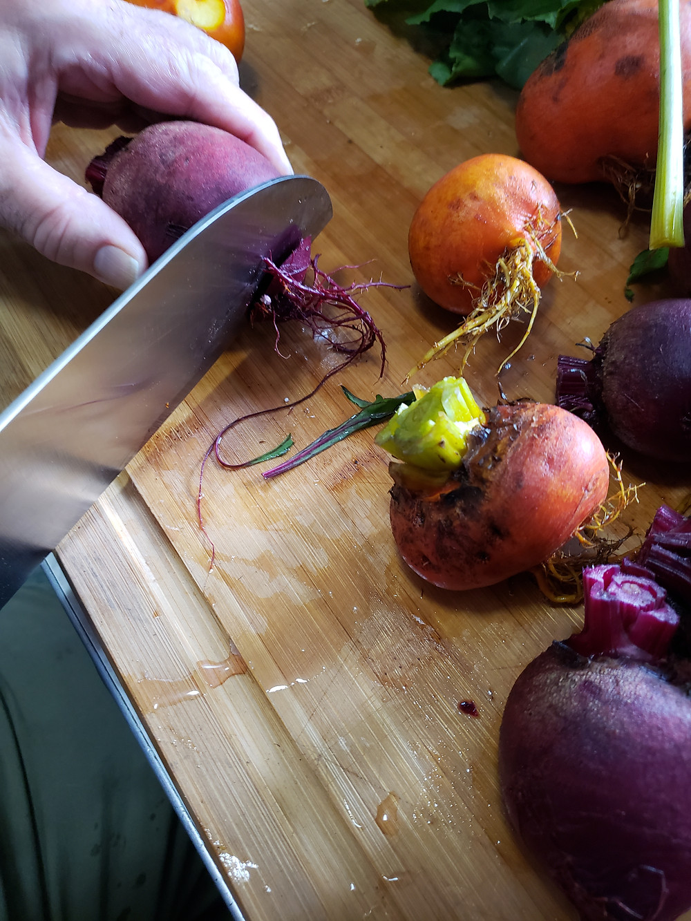 A close-up shot of the beets with greens removed on a wooden cutting board. A left hand holds a beet, while the right holds a knife in mid-process of cutting the root ends off a beet root. End photo ID.