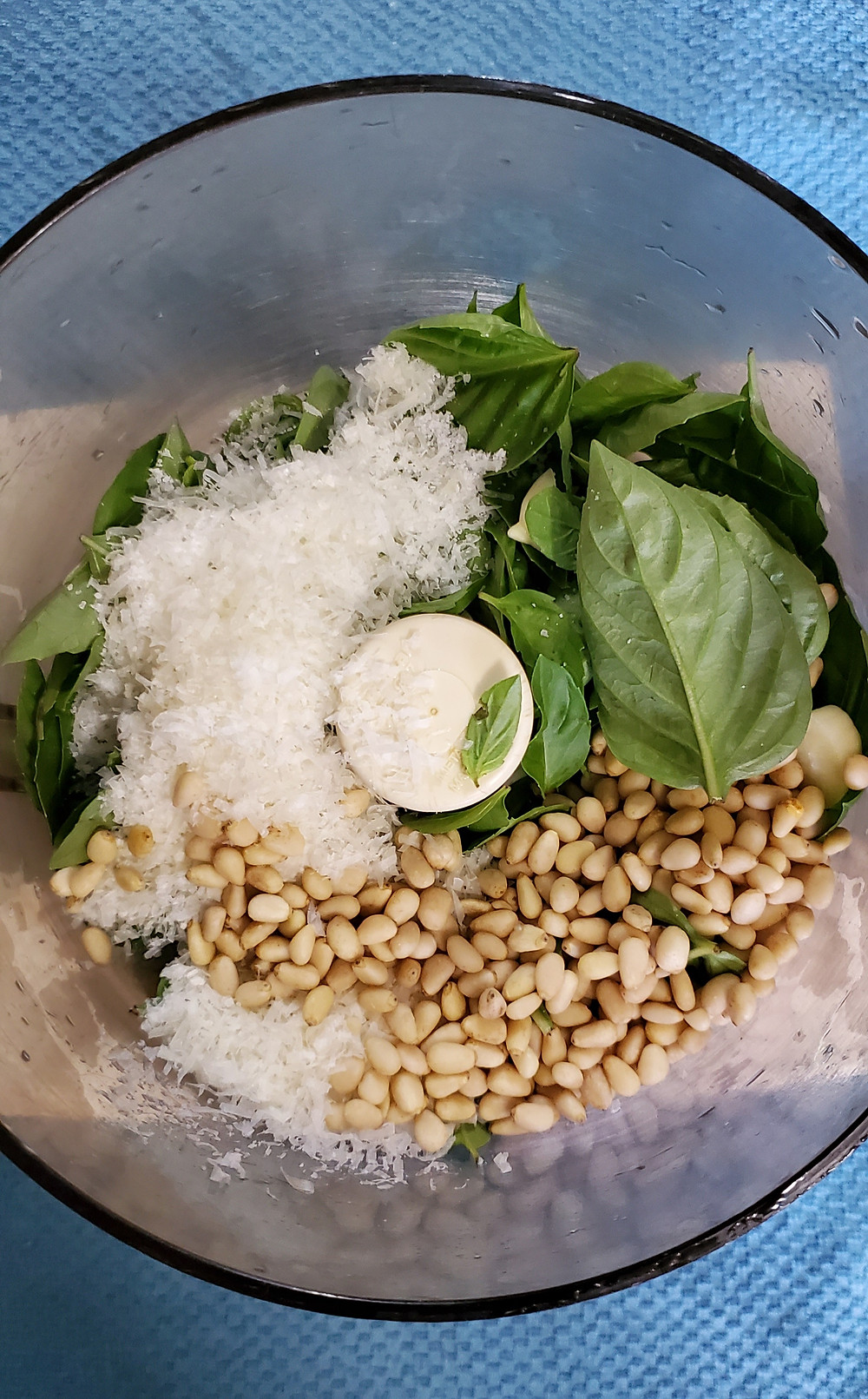 The basket of a food processor rests on a blue background. In it are pine nuts, Parmesan cheese, and basil leaves. End photo ID.