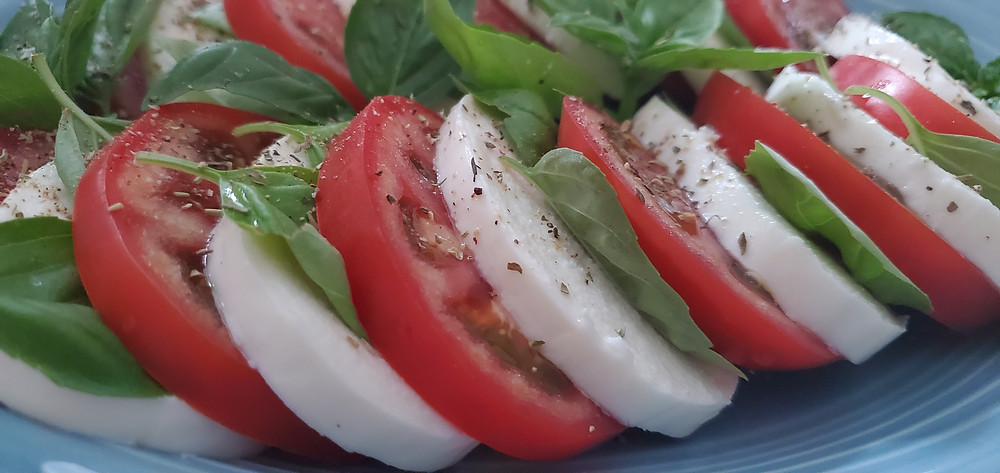 On a blue plate, a closeup of thick slices of fresh mozzarella and tomato are separated by thin leaves of basil. End photo ID.