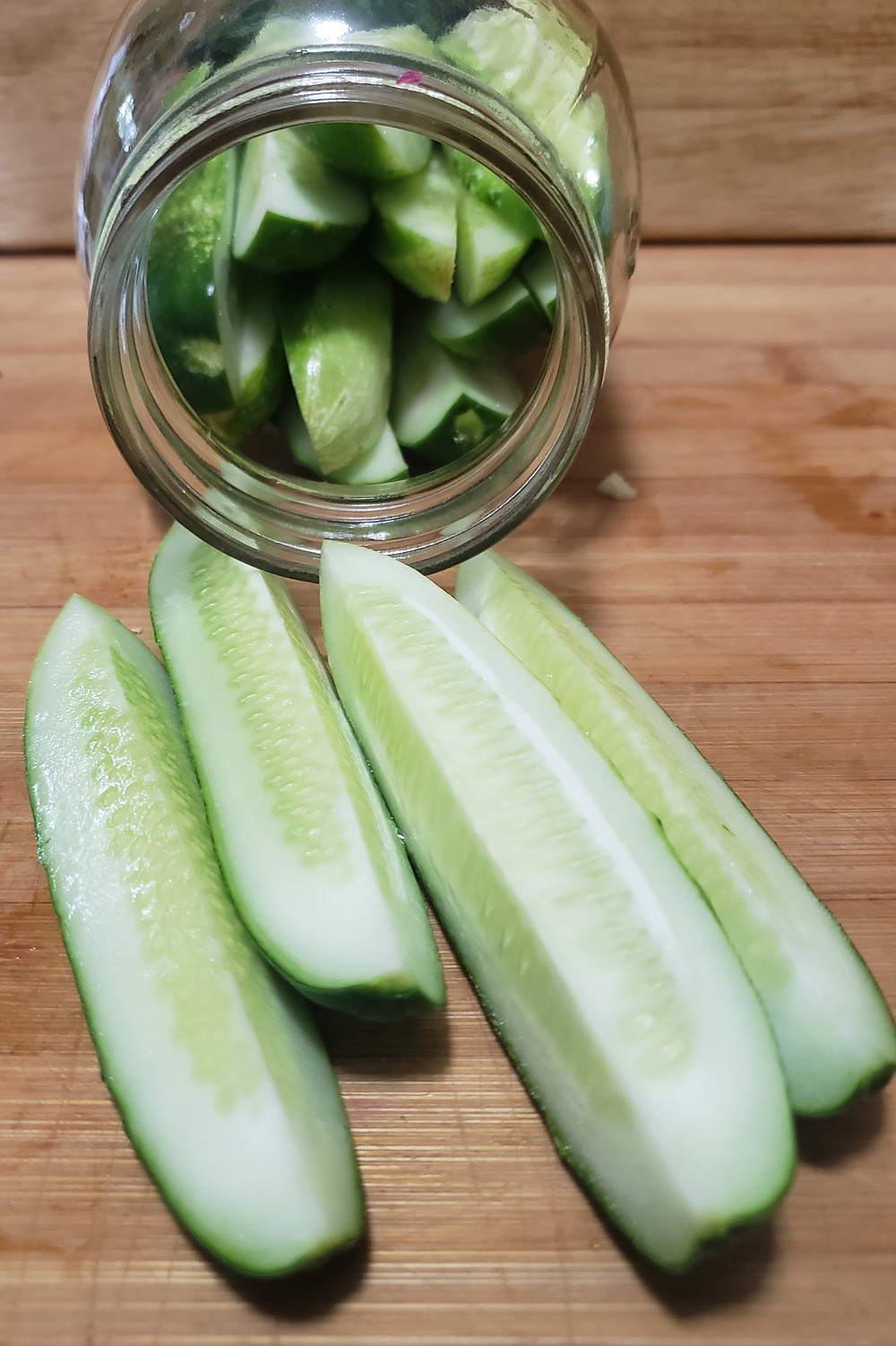 A jar lays on its side with spears of cucumbers inside. In the foreground, four cucumber spears are laying on a wooden cutting board. End photo ID.