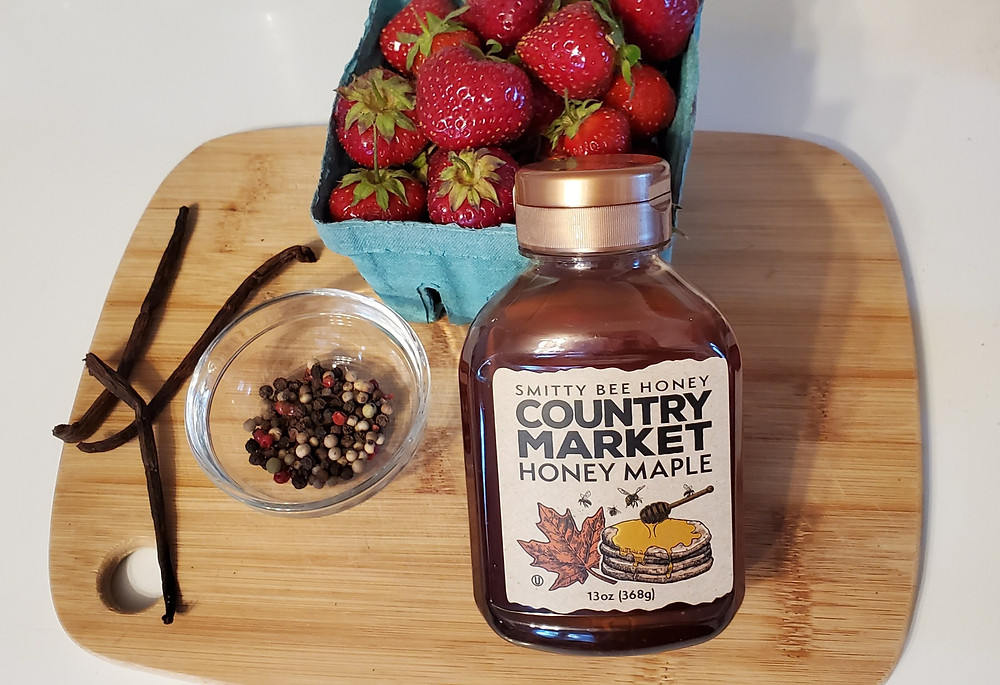 A cutting board sits on a white surface. On the cutting board is a quart of berries, two vanilla beans, a small mixing bowl of rainbow peppercorns, and a jar of honey. End photo ID.