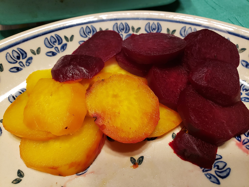 Sliced roasted beets are on a ceramic plate. On the left are golden beets and on the right are classic red beets. End photo ID.