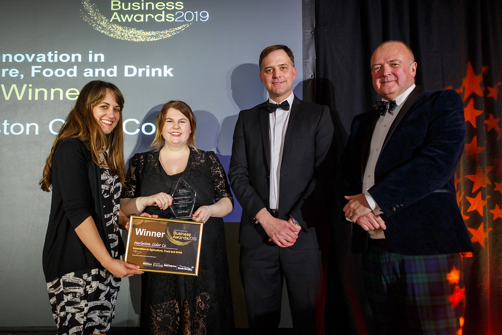 Ruth Comer, Leia Sycamore accept award from New Anglia and South Norfolk Council