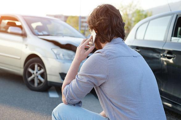 Man calling help after a car crash accid