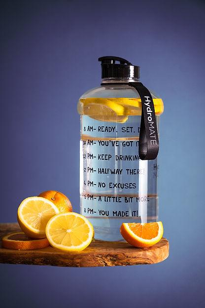 slice-lemon-beside-glass-pitcher-on-wood