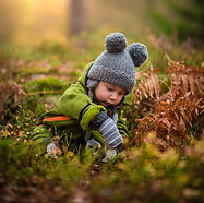 A baby playing in the grass