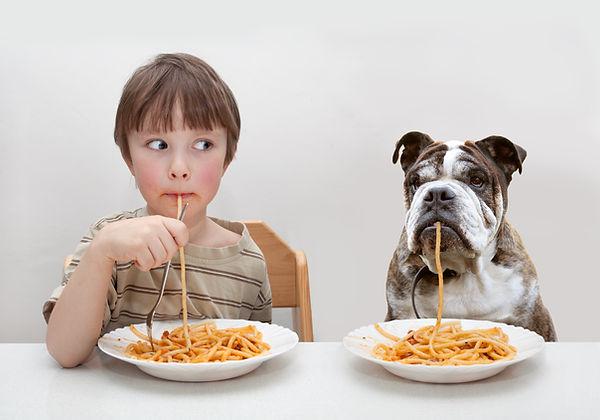 Jongen en hond eten Pasta