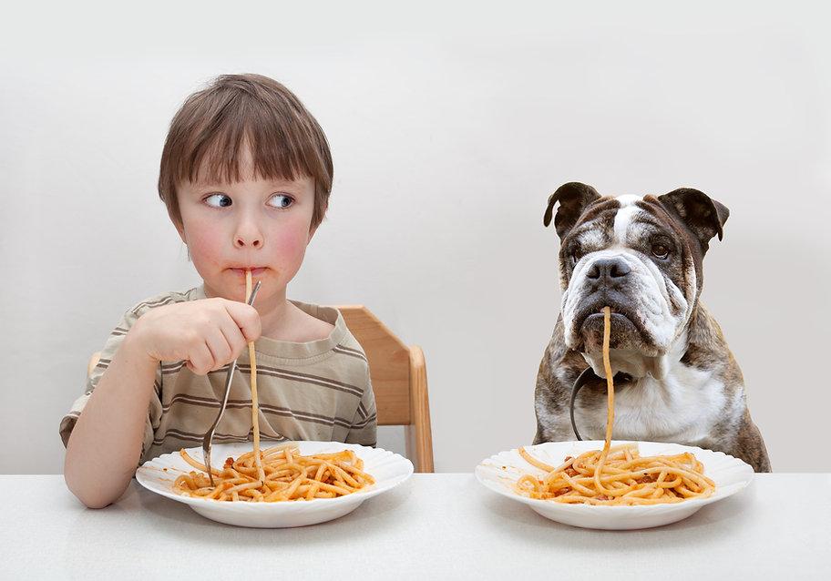 Garçon et chien manger des pâtes