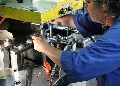 Punch press operator running sheet metal parts