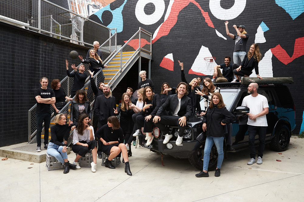 The TABOO team gather outdoors in front of a mural doing fun poses.
