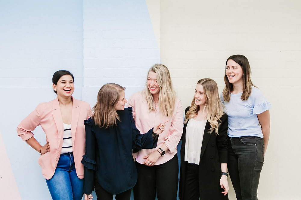 A group of 5 businesswomen stand together laughing.