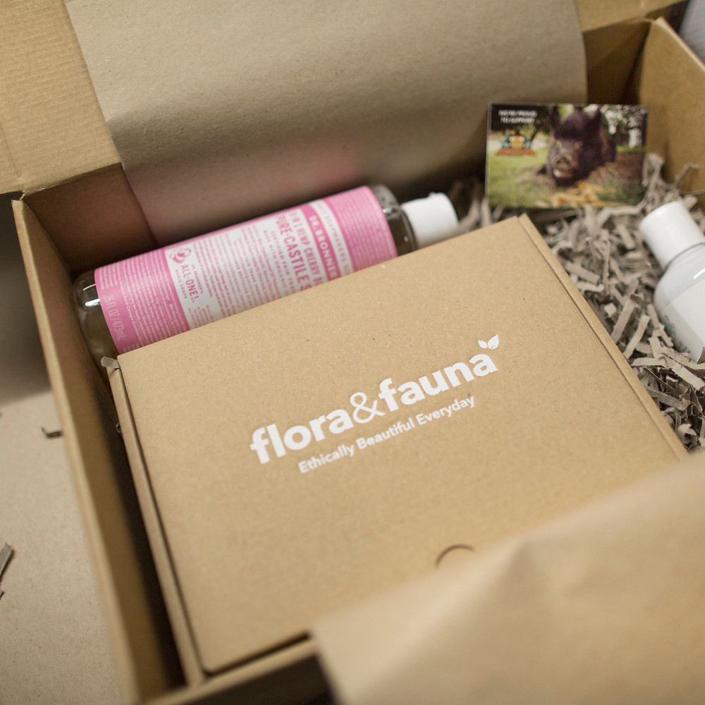 A cardboard box from Flora & Fauna with Dr Bronners and other products inside.