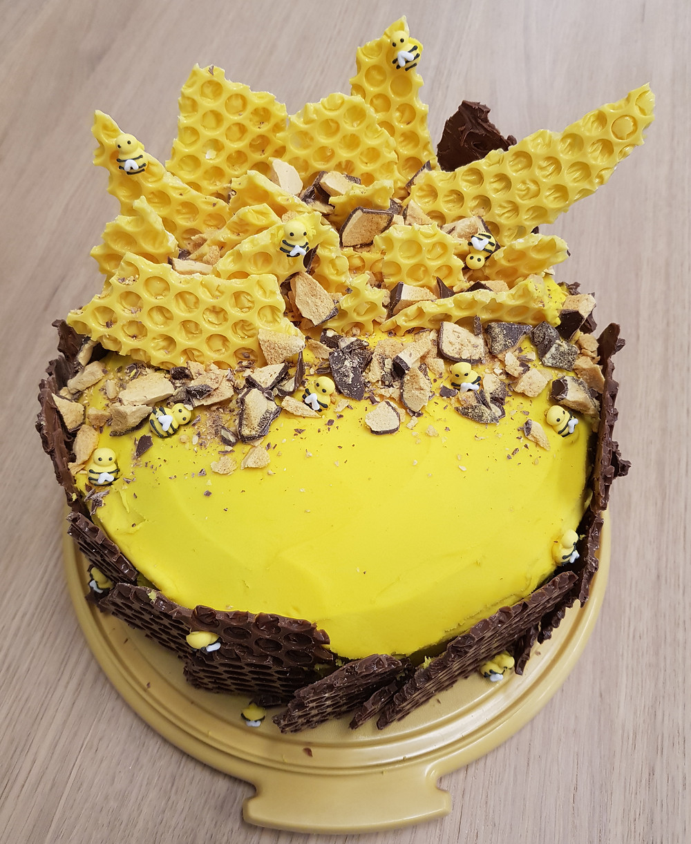 A yellow cake decorated with honeycomb and frosting bees.