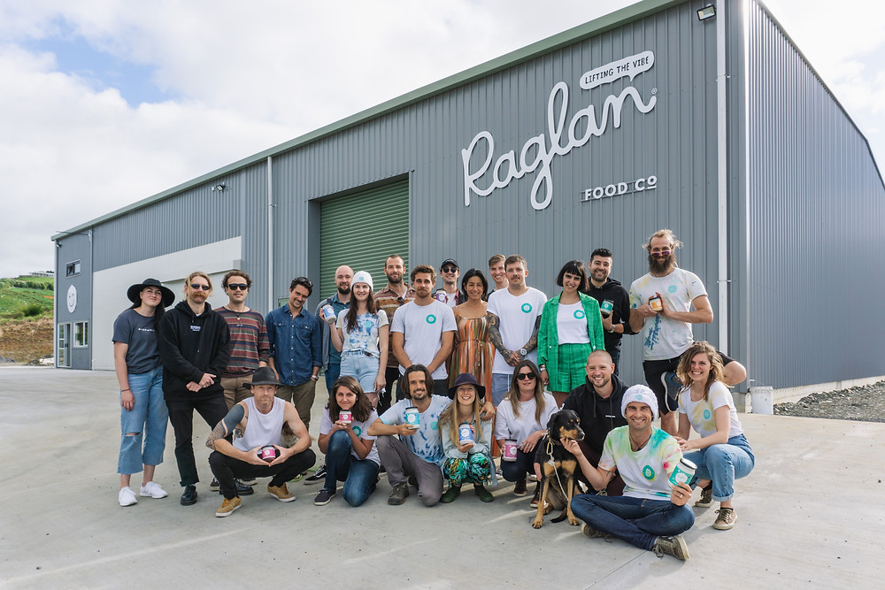 The Raglan Food Co team are gathered in front of the factory, holding jars of yogurt and wearing Raglan stickers.