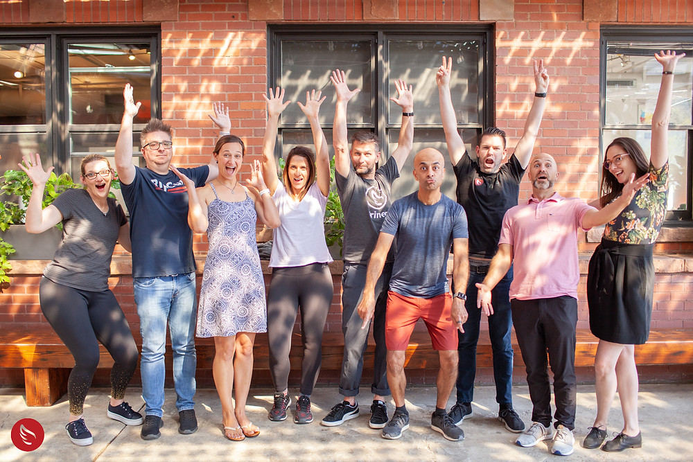 A group of Trineo staff raise their hands in excitement.