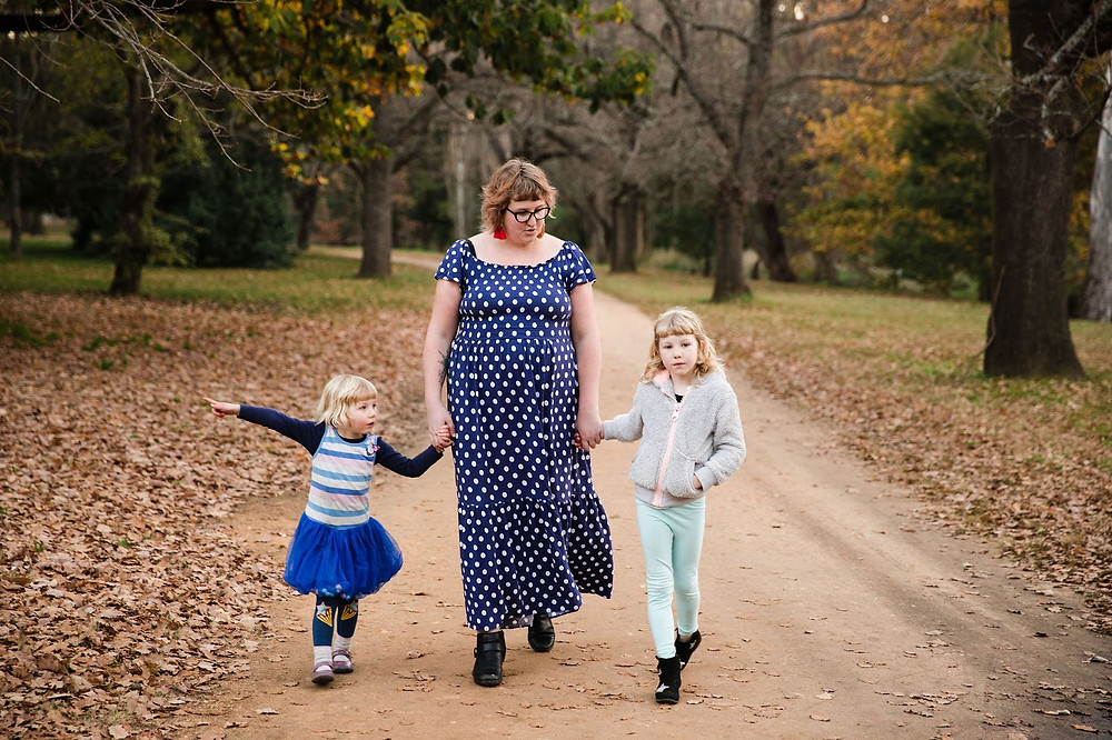 A mother holds hands with her two daughters while walking along a leaf-filled path.