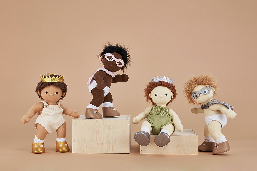 Four small children's dolls are assembled in costumes; two superheroes in diapers, masks, and capes, and two in onesies with crowns.