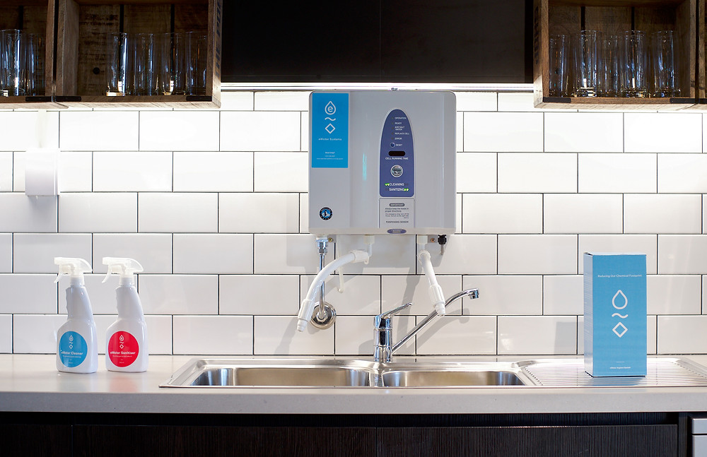 An eWater Systems filter sits above a sink in an office, with 2 spray bottles.