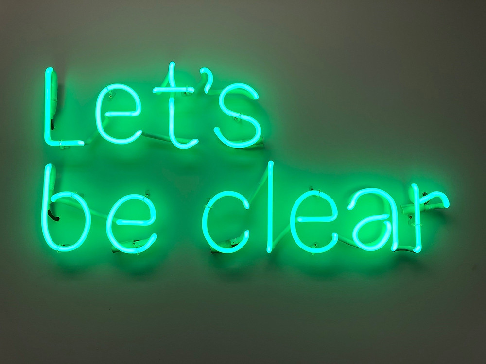 'Let's be clear' sign in neon light.