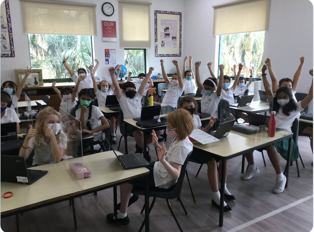 Students at desks raise their arms in a COVID-safe classroom.