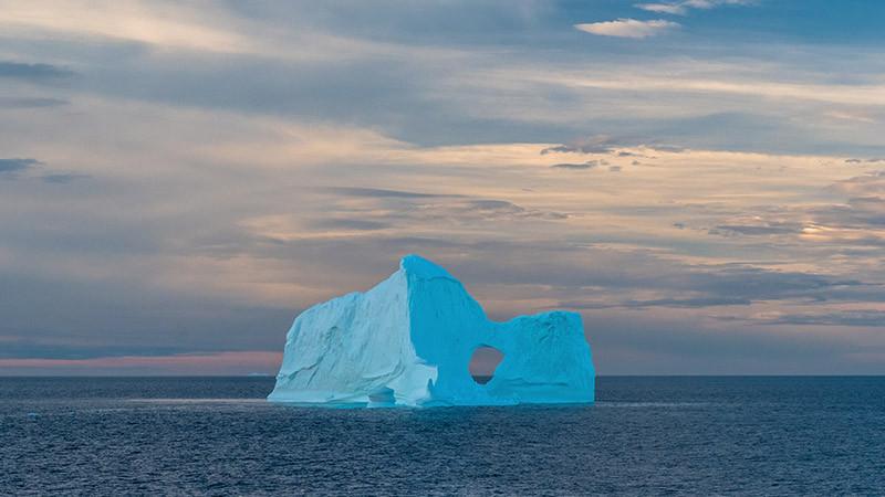 A glacier stands alone in open ocean.