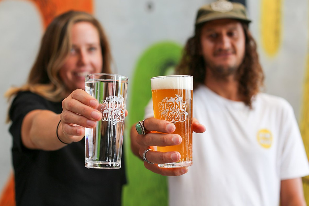 Two people hold Stone & Wood branded glasses, one with water and another with beer.